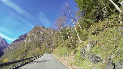 Car drives along mountain pass POV