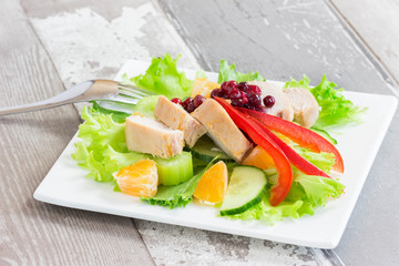 Bird meat mandarin salad in white plate on wooden background