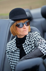 Stylish woman sitting in a Convertible