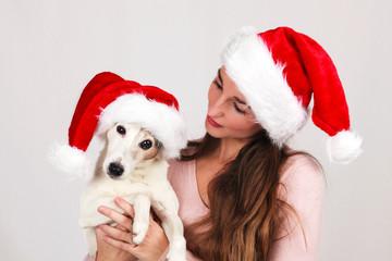Jeune femme avec son chien en bonnet de père noël