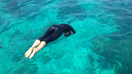 Asian woman jumping in the sea