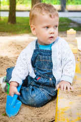 Cute toddler playing with sand in sandbox