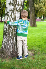Little boy playing hide and seek in park