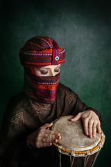 Woman in turban playing drum