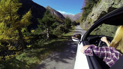POV Woman drives car along mountain road