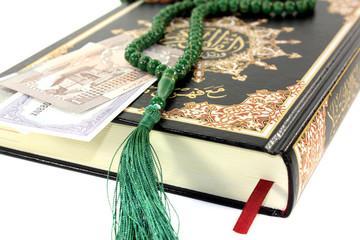 zugeschlagener Koran mit pakistanischer Rupie