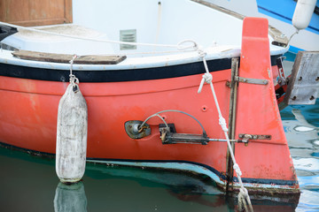 close up of a red hull with white fender