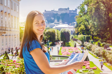 Smiling girl with city map in Mirabell Garden in Salzburg