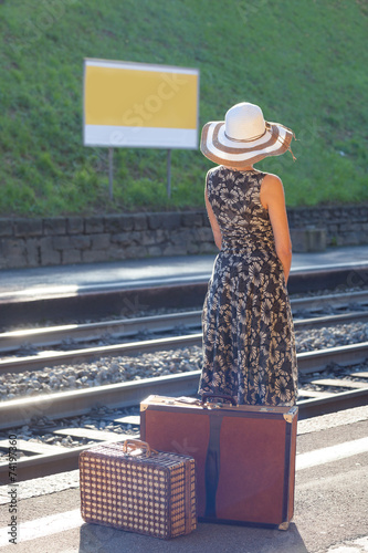 Woman waiting at the railway station with a suitecase