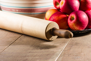 Bowl of apples with a rolling pin