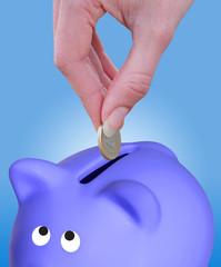 Putting a coin euro in a piggy bank