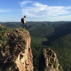 Девушка с рюкзаком на прогулке в горах