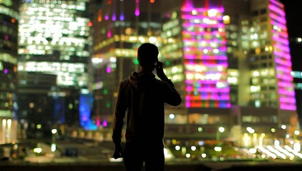 The man stand by sky scraper and call by mobile phone