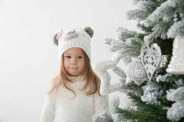 Child girl in bear hat dream at christmas time