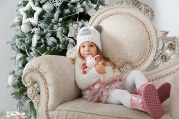 Child girl in bear hat with sheep toy sitting on background of C