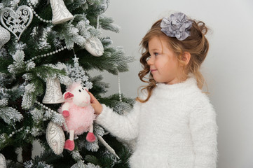Child girl with sheep toy on Christmas tree