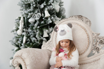 Cute child girl holds sheep toy, Christmas tree