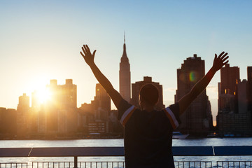 Successful Man with New York Skyline on Background at Sunset