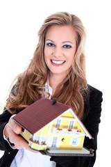 Junge Geschäftsfrau zeigt freundlich Miniatur Traum Haus