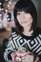 Woman drink cocoa with marshmallows in front of xmas lights