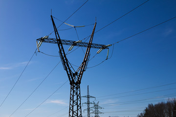 Silhouettes of columns with high-voltage wires