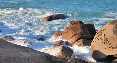 Vagues et écume sur les rochers de la côte de granit rose