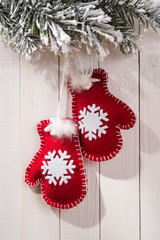 Christmas decorations in the form of mittens on wood background