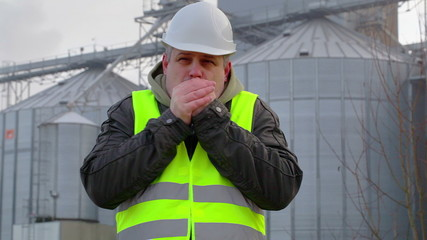 Worker cold at outdoors near the factory in winter