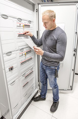 Engineer works in power cabinet
