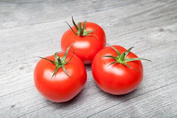 drei tomaten auf grauer platte