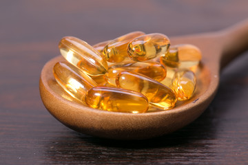 Fish oil capsules in a spoon