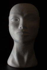 Mannequin head isolated on a black background with side lighting