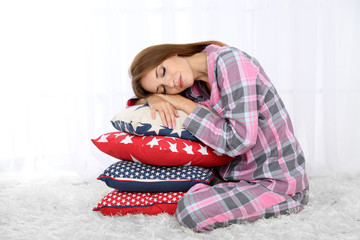Beautiful young girl with pillows  on light background