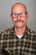 bald man with glasses and a mustache
