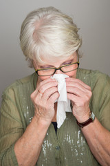 mature woman blowing her nose