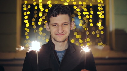 Man with a sparkler in hand bokeh background.