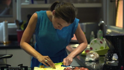 Pretty woman slicing yellow cheese in kitchen at night