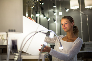 Pretty, young woman choosing the right light for her apartment