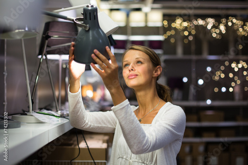 Pretty, young woman choosing the right lamp for her apartment Poster