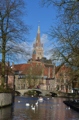 channel with a church tower in belgian city bruges.