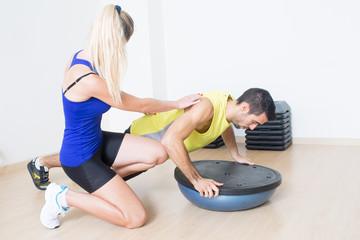 Weiblicher Trainer hilft bei Liegestuetzen