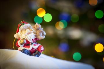 Statuina di Babbo Natale con sfondo di luci colorate