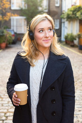 young woman listening to music with a coffee