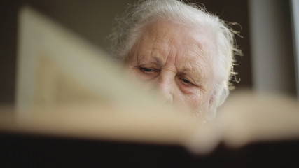 Old human reading a book. Close up
