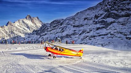Yellow airplane landing to  alpine resort in swiss alps in winte