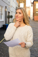 woman holding a document looking thoughtful