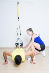 Female trainer explaining suspension training