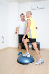 Coach hilft Senior mit Bosu Übung