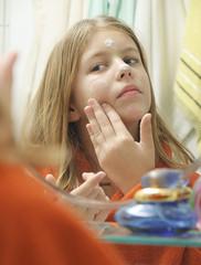 Girl with bathrobe putting cream on face