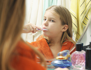 Girl with bathrobe brushing her teeth